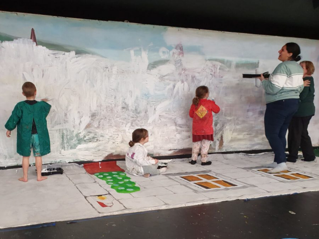 Students painting the backdrop for the play