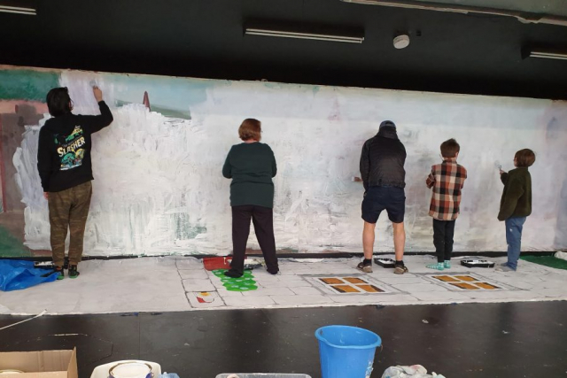 Painting the backdrop for the play