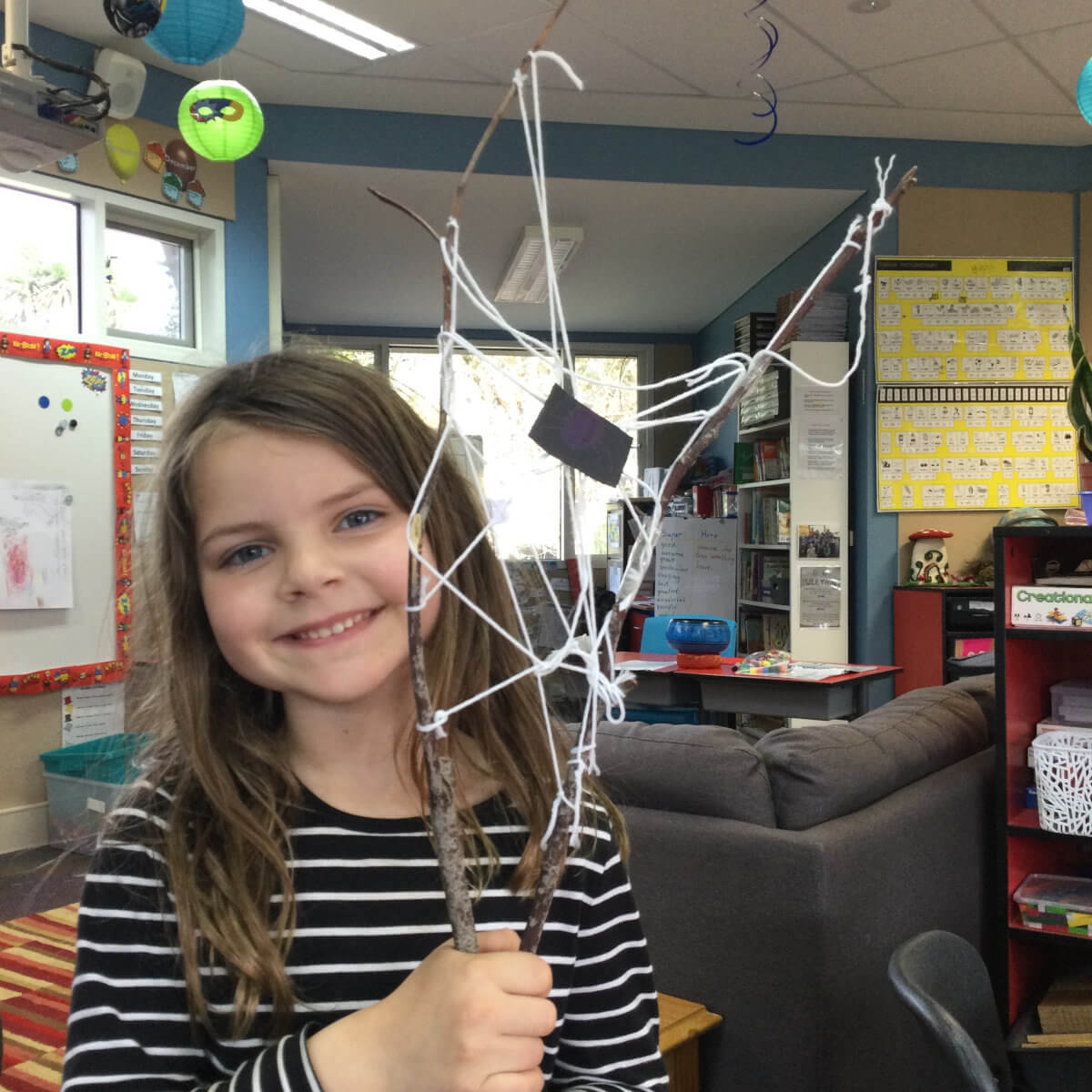 Building a spider web with sticks and string